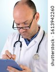 Small photo of Middle aged male doctor is writing a report. Standing in front of a blue background with white bright points to stand out model.