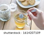 Small photo of Female hand holding spoon and stirring hot tea on wooden table