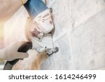 Small photo of Builder man cutting electrical chase in concrete wall with circulation saw drill diamond crown.