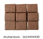 Small photo of Heap of soft chocolate butter cookie with white creamy filling isolated. Brown quadratic soft biscuits, square cookies or fresh sweet cocoa buns closeup