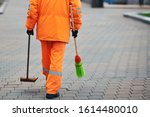 Municipal worker sweep city street,  janitor with broomstick and scoop for garbage in hands. Municipal worker in orange uniform collecting garbage from road and sidewalk. City cleaning service