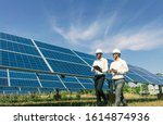 Small photo of The solar farm(solar panel) with two engineers walk to check the operation of the system, Alternative energy to conserve the world's energy, Photovoltaic module idea for clean energy production.