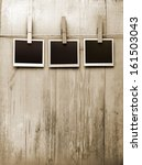 Stock photo snapshots hanging from a rope on a wooden background 161503043