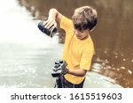 A Boy Stands In The River On...