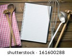 top view of recipe book with kitchenware on wooden table - stock photo