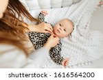 young mom dresses her baby...   Shutterstock . vector #1616564200