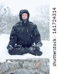 A young man meditates in the lotus position on the snow - stock photo