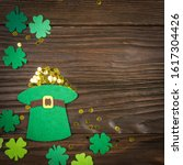Small photo of Happy Saint Patrick's mockup of handmade felt hat full of gold and shamrock clover leaves on wooden background