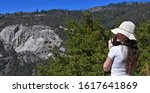 Yosemite National Park, California / September 9, 2018: California's Sierra Nevada mountains. It's famed for its giant, ancient sequoia trees. White Caucasian girl wearing a hat taking a picture. - stock photo