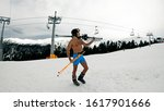 Naked nude male in shorts, helmet, goggles and boots standing on slope under ski lift