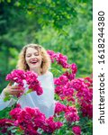 Small photo of Young smiling woman surrounded rose flowers. Tender girl enjoing summer time and roseblush blossom. Rosier concept. Pink summer flowers blossom. Happy woman holding roses