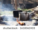Small photo of Cooking in two sooty old cauldrons on bonfire with smoke at forest in sunny summer day