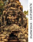 Small photo of bas relief face a smiling Buddha carvings on the wall background texture - complex Angkor wat Cambodia.
