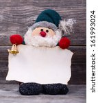 Santa Claus toy holding empty paper against wooden background - stock photo