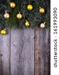 Christmas fir tree with golden decoration on a wooden board - stock photo