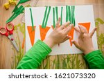 Small photo of child is doing applique of carrots. each carrot has number and an equivalent number of stems