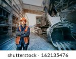 Worker In A Helmet Stands Near...