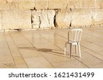 Small photo of An empty chair at the Kotel Wailing Western Wall, a remnant of the ancient wall that surrounded the Jewish Temple's the most sacred site recognized by the Jewish faith outside of the Temple Mountain.
