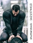 Small photo of tired young strong athlete male with beard wearing black sportswear sitting on iron barbell with grimace of pain on his face during heavy muscle workout