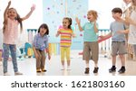 Small photo of Cheerful kids stand semicircle on floor in kindergarten or daycare centre. Preschoolers have fun indoors, playing games