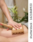 Small photo of Closeup of the maderotherapy anti-cellulite massage with wooden roller massager