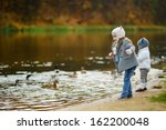 Two Little Girls Feeding Ducks...