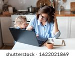 Small photo of Working mother in home office. Unhappy woman and child using laptop. Sad and angry daughter needs attention from busy exhausted mom. Freelancer workplace in kitchen. Female business. Lifestyle moment.