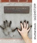 Small photo of Chicago, IL September 19, 2019, Frank Thomas professional baseball player hand prints in cement at the Chicago Sports Authority Wall of Fame 620 North LaSalle Drive compared to my hand size