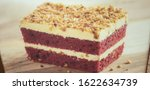 Small photo of red velvet cake topped with peanuts and a garish of cream