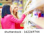 beautiful women choose personal care product in supermarket - stock photo