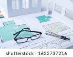 Small photo of Bureau of Architecture. Drawings on the desk of an engineer. Workplace of the architect. Design of residential premises. Development of drawings of premises. Layout of the rooms. Building.