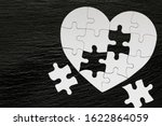 Small photo of Heart-shaped jigsaw puzzle on color background. Puzzle heart on wooden background. A missing piece of the heart puzzle. Heart shape jigsaw puzzle. Puzzles in the shape of a heart.