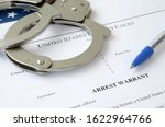 Small photo of District Court Arrest Warrant court papers with handcuffs and blue pen on United States flag. Concept of permission to arrest suspect