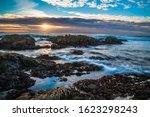 Sunset  And Waves On Rocks At...