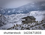 A cabin in the mountains in a snow storm with elk  - stock photo