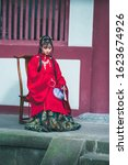 Portrait of ancient girl with long hair wearing Chinese Ming hanfu suit sits on wooden chair.