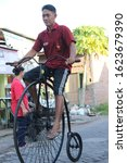 Small photo of Asian men cycling penny farthing (bicycles that use large front wheels). surabaya - indonesia. November 2019