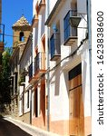 Small photo of Town houses in a narrow street with a church bell tower to rear, Ubeda, Andalucia, Spain.