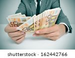 a man wearing a suit sitting in a desk counting euro bills - stock photo