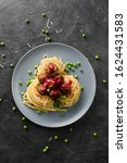 Small photo of Healthy savory food Nordic style. Linguine pasta with homemade meatballs, green peas and lingonberry sauce on grey plate on black background top view copy space