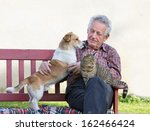 Senior Man With Dog And Cat On...