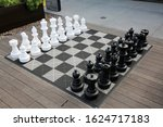 Chess Kit. Giant Chess Game in a public area. People can play a Giant Chess Game as they enjoy a nice day outside. Chess is a game that has been enjoyed for hundreds of years.