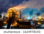 Small photo of Aerial view of metallurgical plant blast furnace at night with smokestacks and fire blazing out of the pipe. Industrial panoramic landmark with blast furnance of metallurgical production