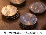 Small photo of Multiple stacks of American currency quarter dollar quarters on a wooden table.
