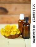 Small photo of Dandelion tincture. Herbal tincture. Medicinal herbs. Medicinal tincture in brown bottles and dandelion flowers on a wooden background.infusion of healing herbs. Homeopathy