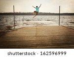 teen boy jumping off a dock | Shutterstock . vector #162596999