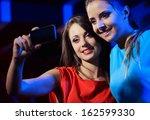 two happy women at nightclub... | Shutterstock . vector #162599330