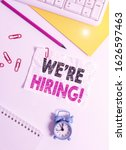 Small photo of Text sign showing We Re Hiring. Conceptual photo recently employ someone or pay him to do particular job Flat lay above white blank paper with copy space for text messages.