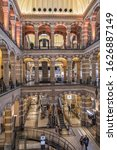Small photo of AMSTERDAM, NETHERLANDS - AUGUST 22, 2019: Interior of Magna Plaza Shopping Center. Magna Plaza, formerly known as Amsterdam Main Post Office, is a monument part of Dutch Top 100 heritage sites.