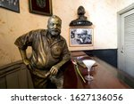 Small photo of November 26, 2019, Havana, Cuba: Glass of Daiquiri cocktail and statue of American writer Ernest Hemingway in the bar El Floridita in Havanna